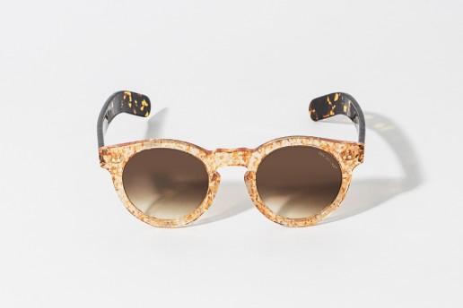 Occhiali da sole in celluloide con intarsi arancio leggermente glitterato. Aste color tartarugato. Lente color marrone sfumato, protezione 100% dai raggi UV. Misure 46 – 23 asta 150